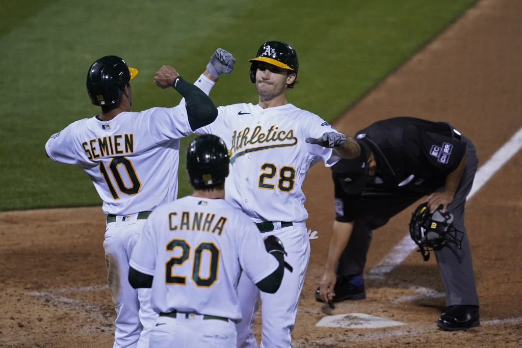 Oakland Athletics' Matt Olson (28) is greeted by Marcus Semien (10) and Mark Canha (20) after hitting a three-run home run off San Francisco Giants st...