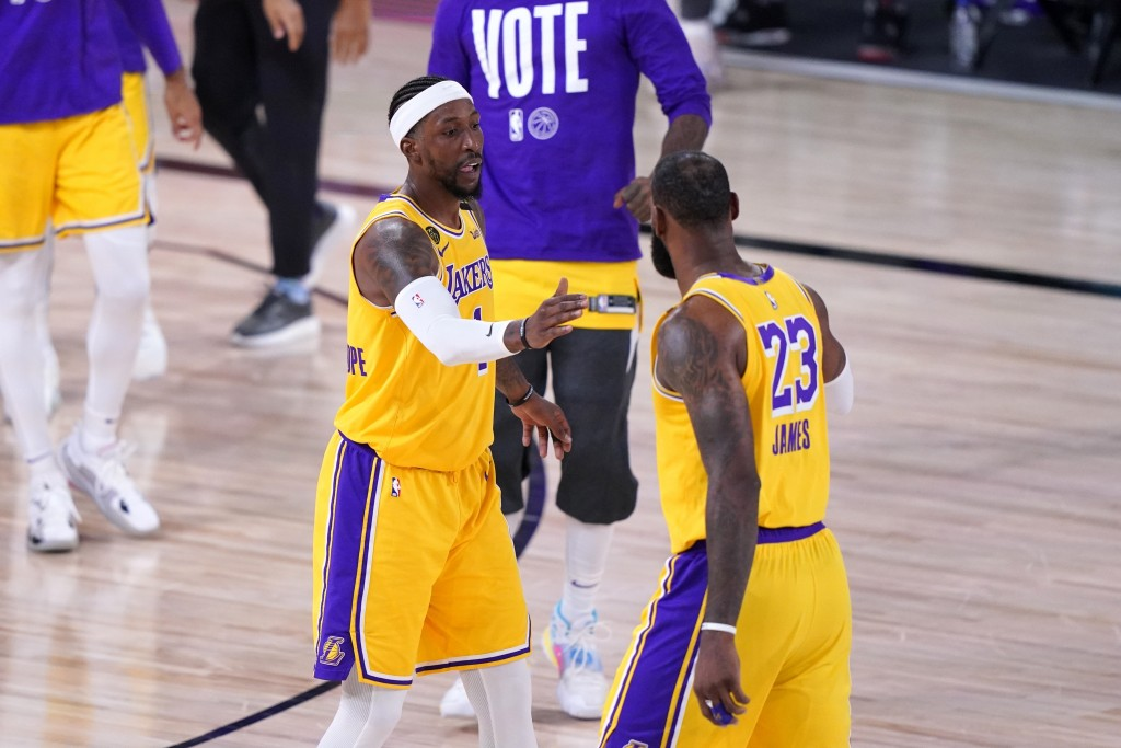 Los Angeles Lakers' Kentavious Caldwell-Pope, left, greets LeBron James, right, on the court during a time out from play in the second half an NBA con...