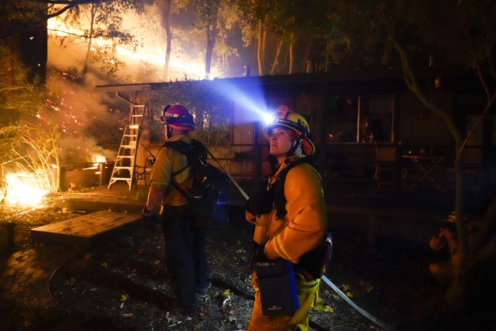 Firefighters monitor the advance of the CZU August Lightning Complex Fire in the backyard of a home Friday, Aug. 21, 2020, in Boulder Creek, Calif.  F...