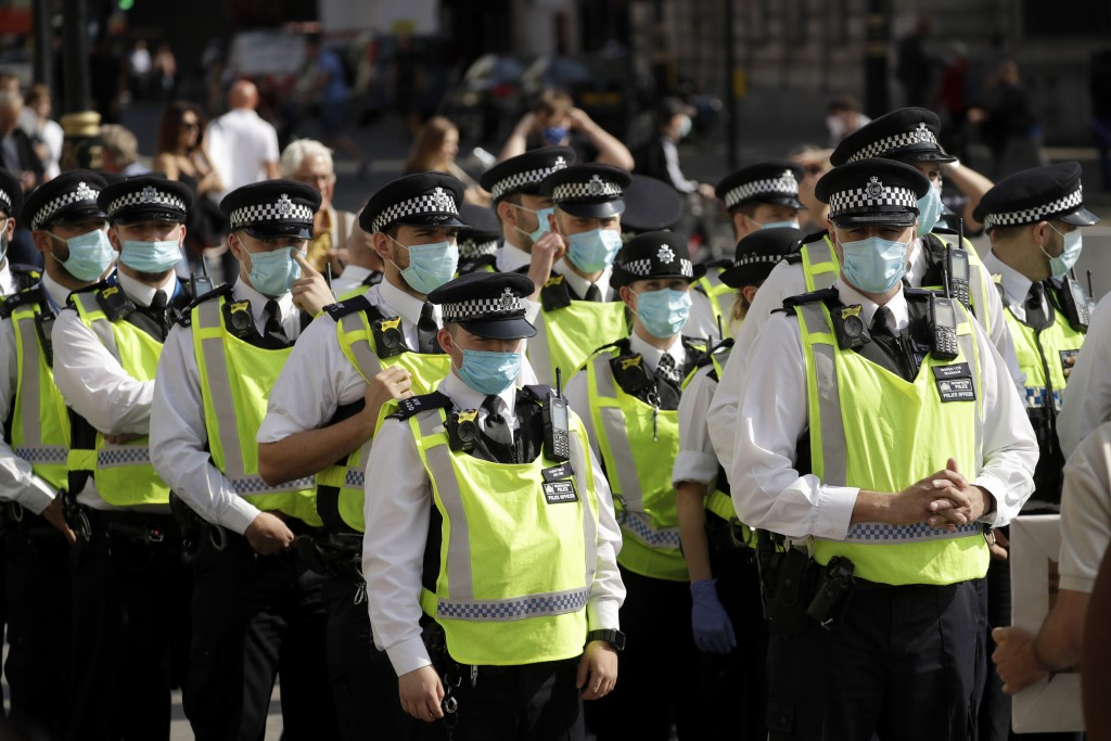 "Police officers wearing face masks stand next to a ""Resist and Act for Freedom"" protest against a mandatory coronavirus vaccine, wearing masks, social..."