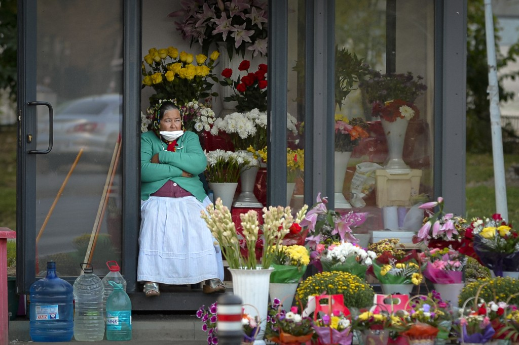 A flower vendor with a mask for protection against the COVID-19 infection, partially covering her face watches people passing by in Bucharest, Romania...