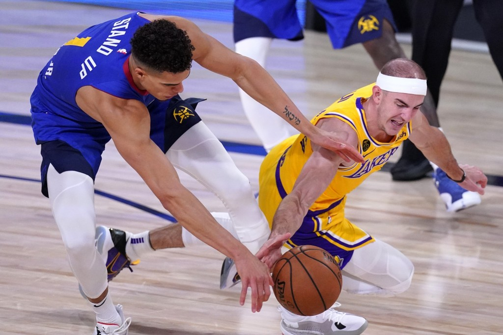 Denver Nuggets' Michael Porter Jr., left, and Los Angeles Lakers' Alex Caruso, right, compete for control of a loose ball during the second half an NB...