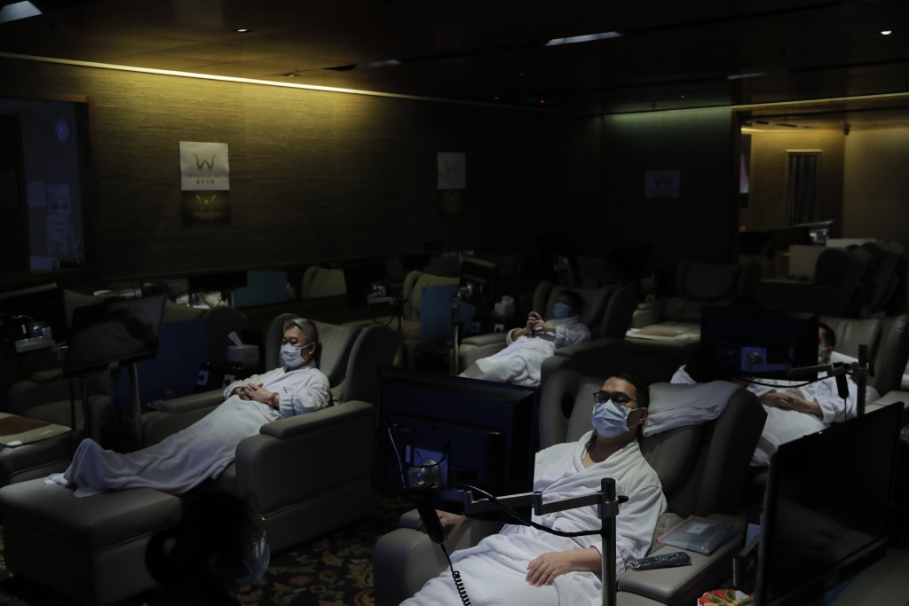 Staff members wearing face masks demonstrate safety measures to the media as the massage spa plans for reopening in Hong Kong, Thursday, Sept. 17, 202...