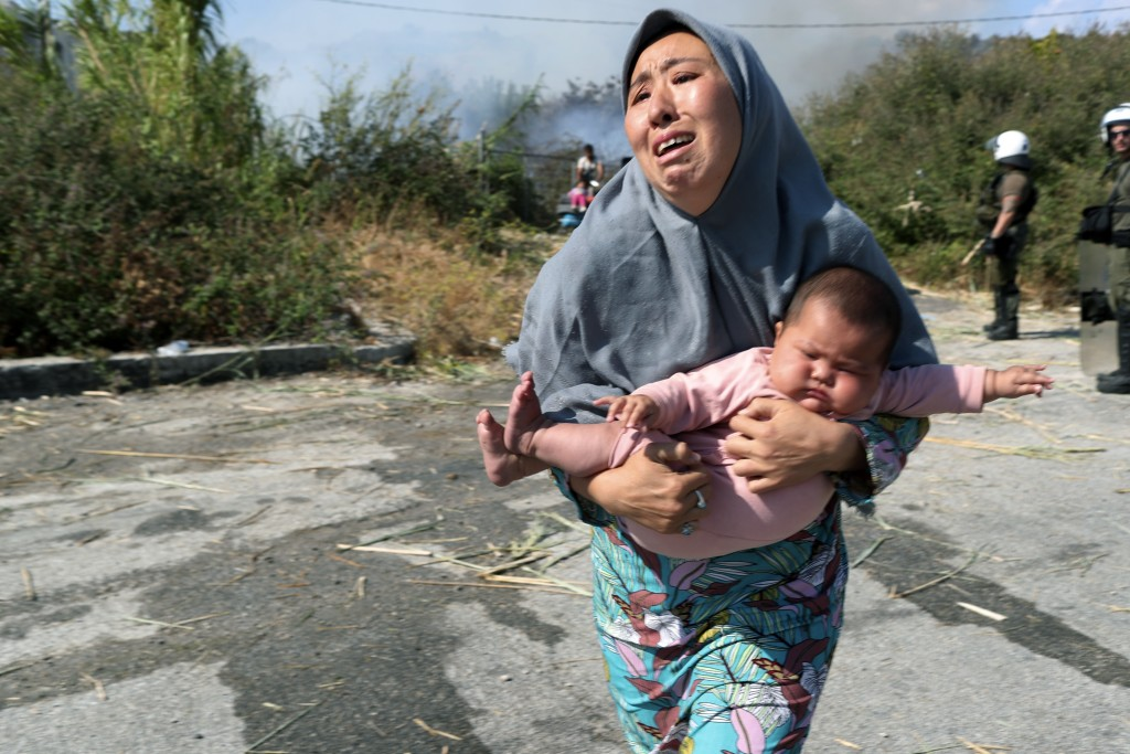 A migrant holds her baby as she runs to avoid a small fire in a field near Mytilene town, on the northeastern island of Lesbos, Greece, Saturday, Sept...