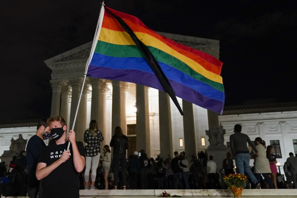 People gather at the Supreme Court Friday, Sept. 18, 2020, in Washington, after the Supreme Court announced that Supreme Court Justice Ruth Bader Gins...