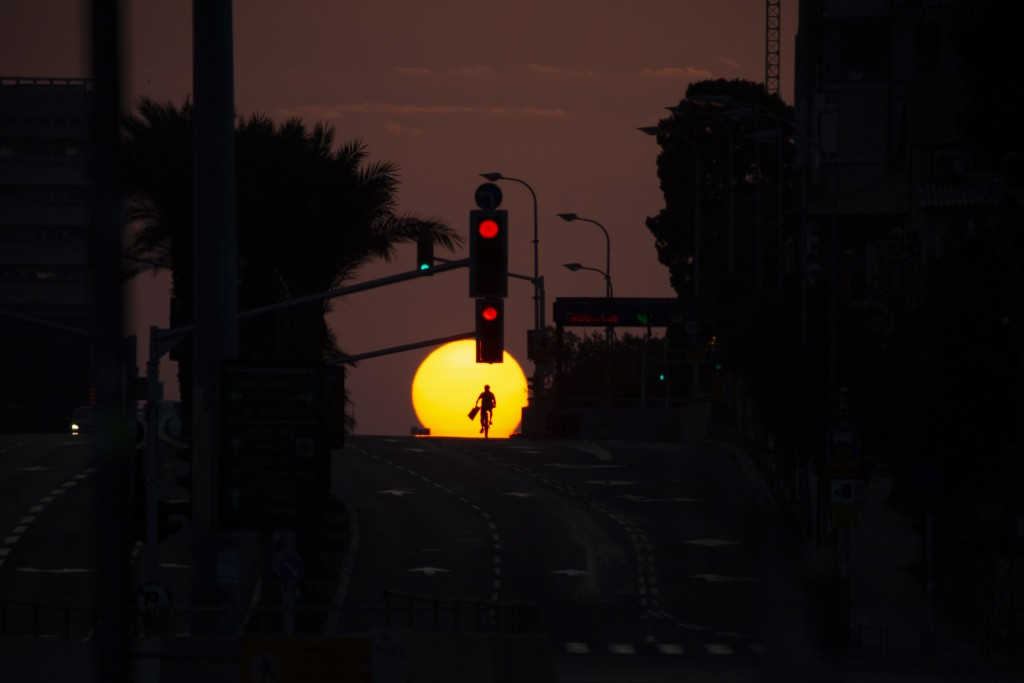 A person rides a bicycle on an empty street during sundown on the first day of a three-week lockdown in Tel Aviv, Israel, Friday, Sept. 18, 2020. Isra...