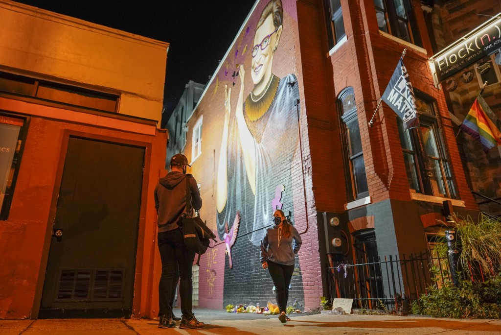People gather under a mural of Supreme Court Justice Ruth Bader Ginsburg in the U Street neighborhood in Washington, Friday, Sept. 18, 2020, after the...