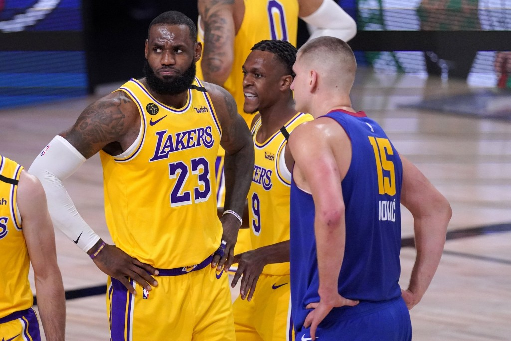 Los Angeles Lakers' LeBron James (23), Rajon Rondo (9) and Denver Nuggets' Nikola Jokic, wait for play to restart during the second half an NBA confer...