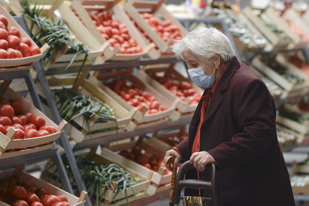 An elderly lady wearing a mask for protection against COVID-19 infection looks at vegetables after the opening of a market selling Romanian food produ...