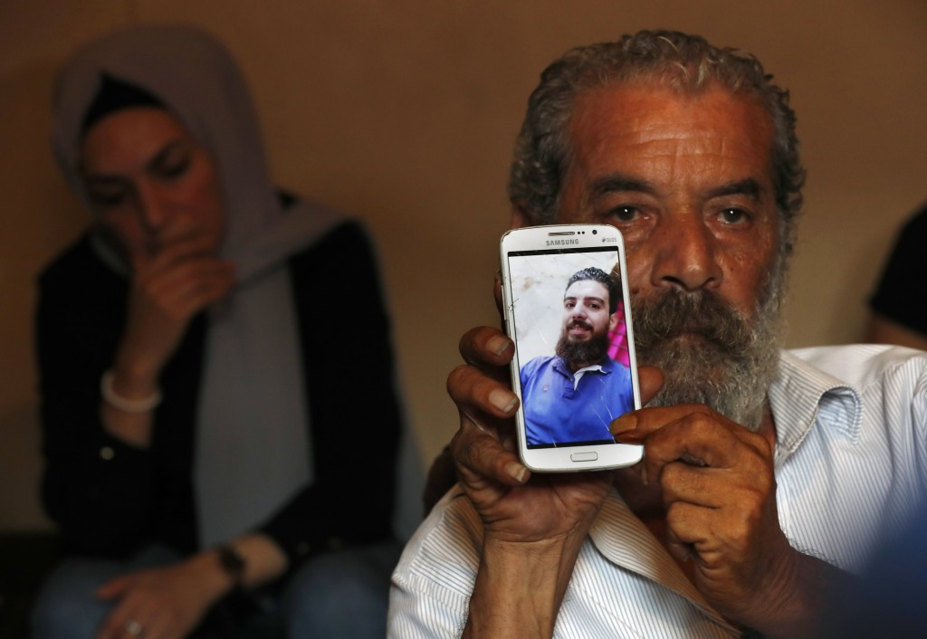 Lebanese Khaldoun Mohammed, 58, shows a portrait of his son Mohammed, 27, who is still missing at sea while he was trying with other migrants to reach...
