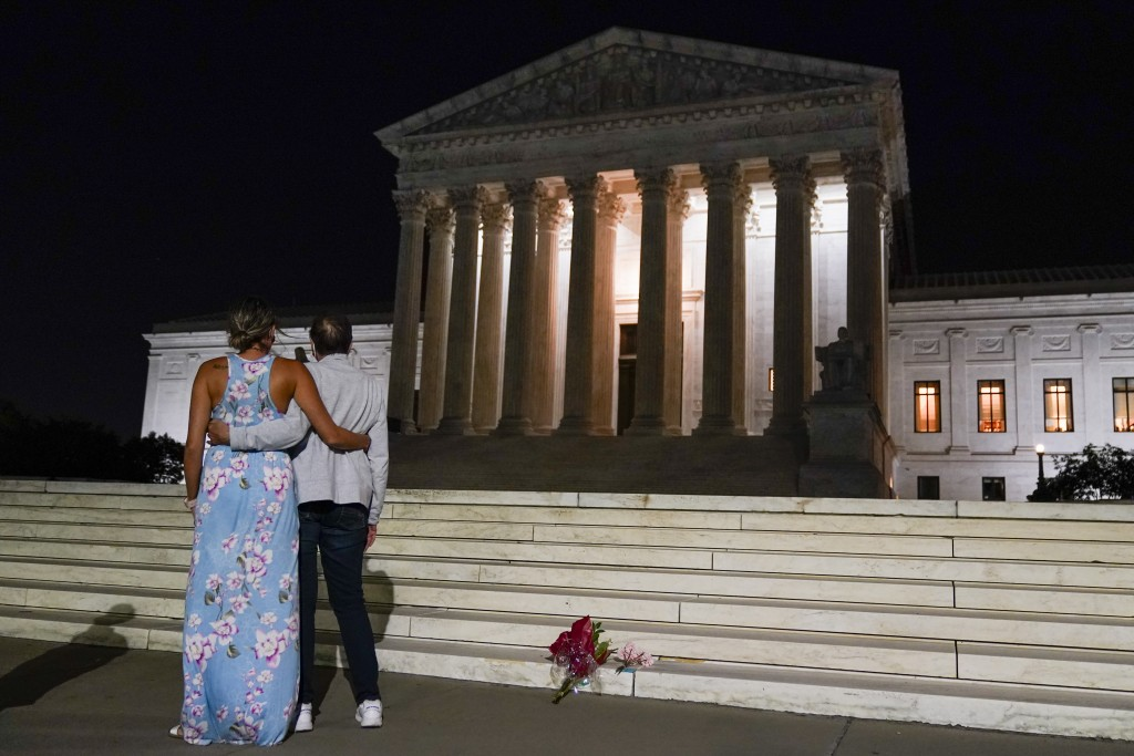 A couple pauses outside the Supreme Court Friday, Sept. 18, 2020, in Washington, after the Supreme Court announced that Supreme Court Justice Ruth Bad...