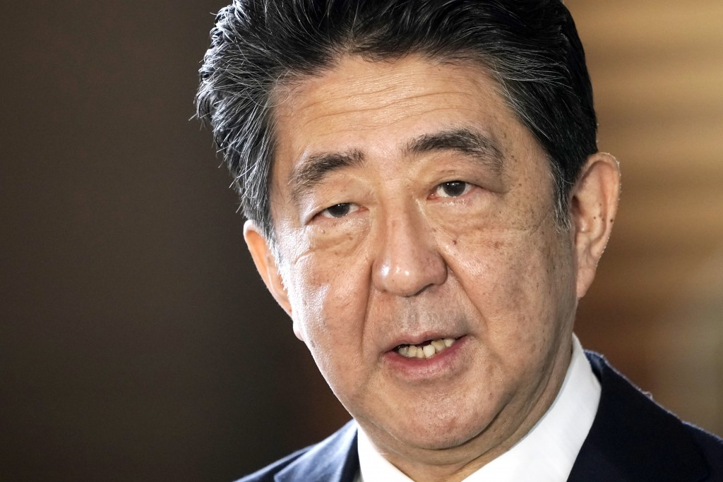 FILE - In this Sept. 16, 2020, file photo, Japan's outgoing Prime Minister Shinzo Abe speaks to the media as he arrives at the prime minister's office...