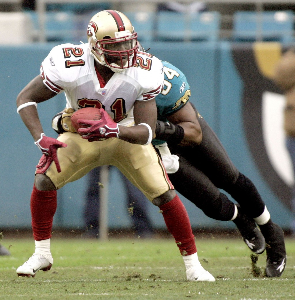 FILE - In this Dec. 18, 2005, file photo, San Francisco 49ers running back Frank Gore, left, is tackled by Jacksonville Jaguars defender Mike Peterson...