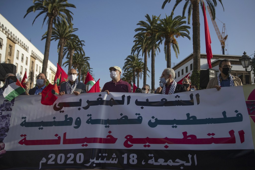 People hold a banner during a protest against normalizing relations with Israel, in Rabat, Morocco, Friday, Sept. 18, 2020. Despite a government ban o...