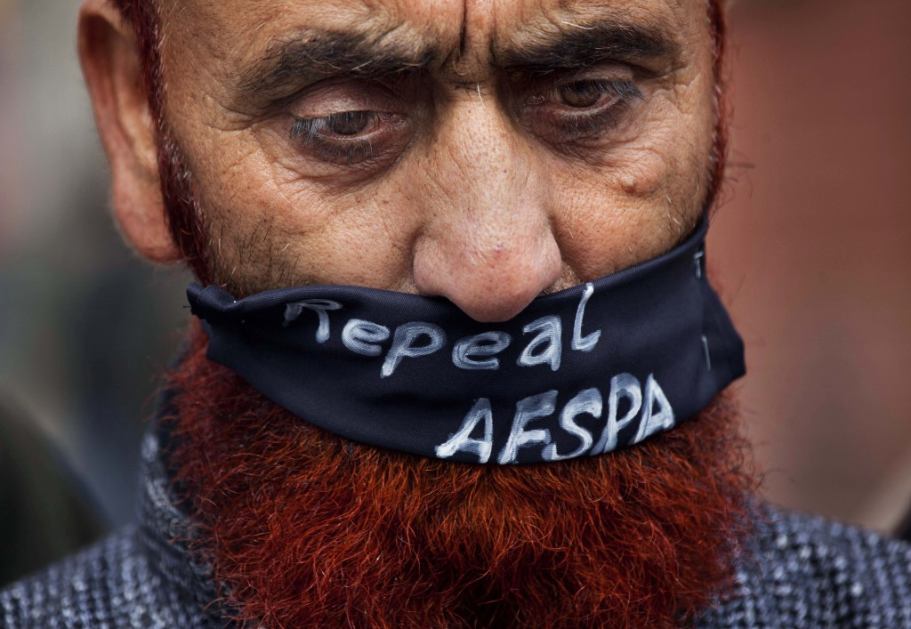 FILE - In this  Saturday, Feb. 15, 2014, file photo, a relative of a missing Kashmiri wears a scarf asking for the Armed Forces Special Powers Act (AF...