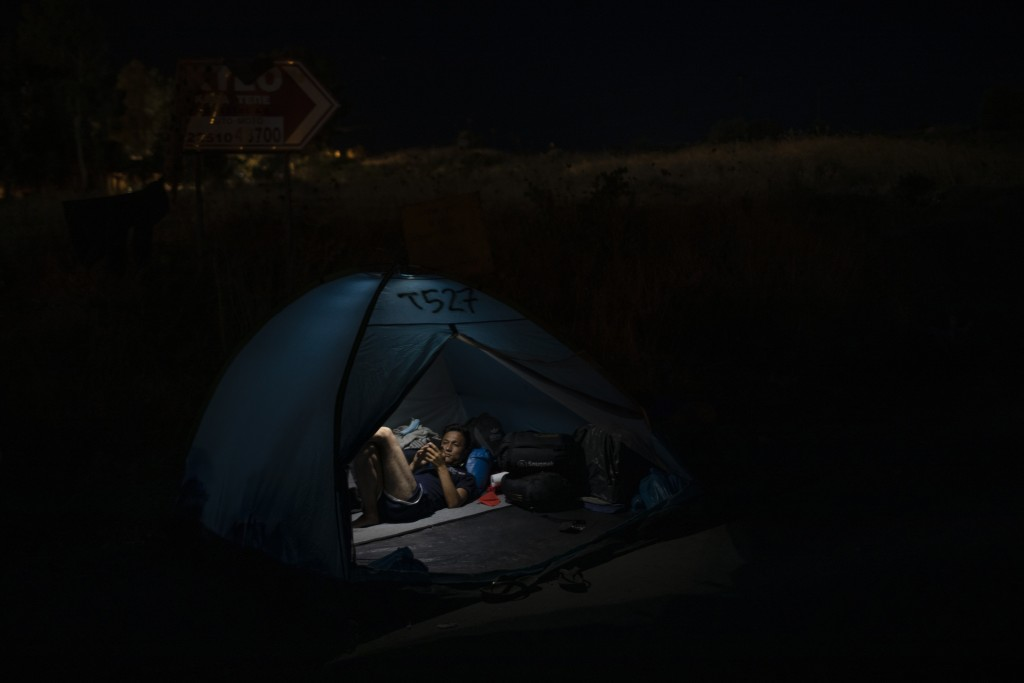 A migrant sits inside his tent on a road leading from Moria to the capital of Mytilene, on the northeastern island of Lesbos, Greece, Thursday, Sept. ...