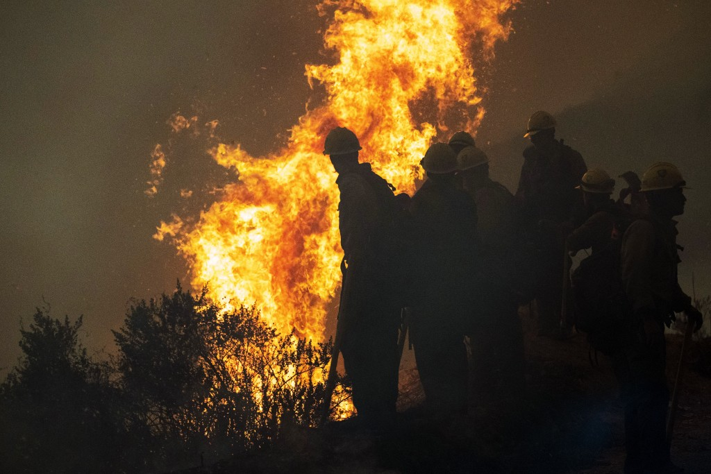 Firefighters monitor a controlled burn along Nacimiento-Fergusson Road to help contain the Dolan Fire near Big Sur, Calif., Friday, Sept. 11, 2020. (A...