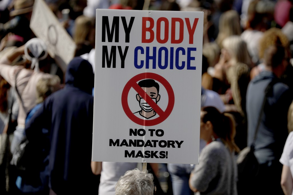 "A protester holds up a placard as they take part in a ""Resist and Act for Freedom"" protest against a mandatory coronavirus vaccine, wearing masks, soc..."