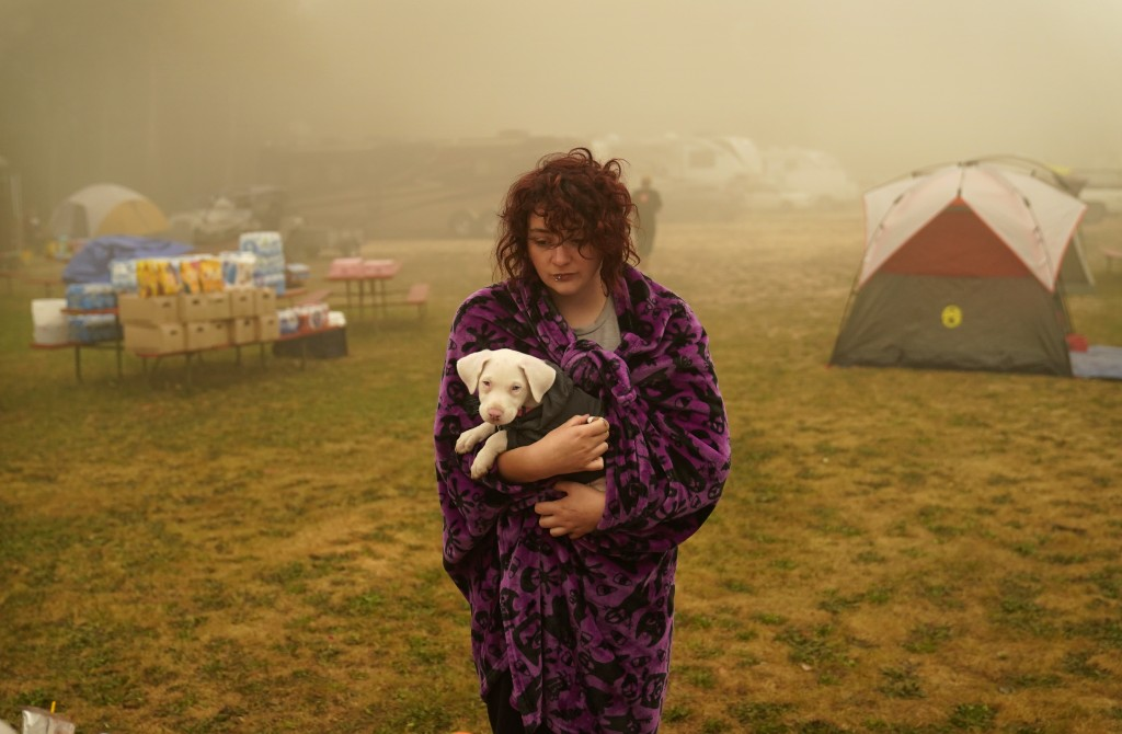 Shayanne Summers holds her dog, Toph, while wrapped in a blanket after several days of staying in a tent at an evacuation center at the Milwaukie-Port...