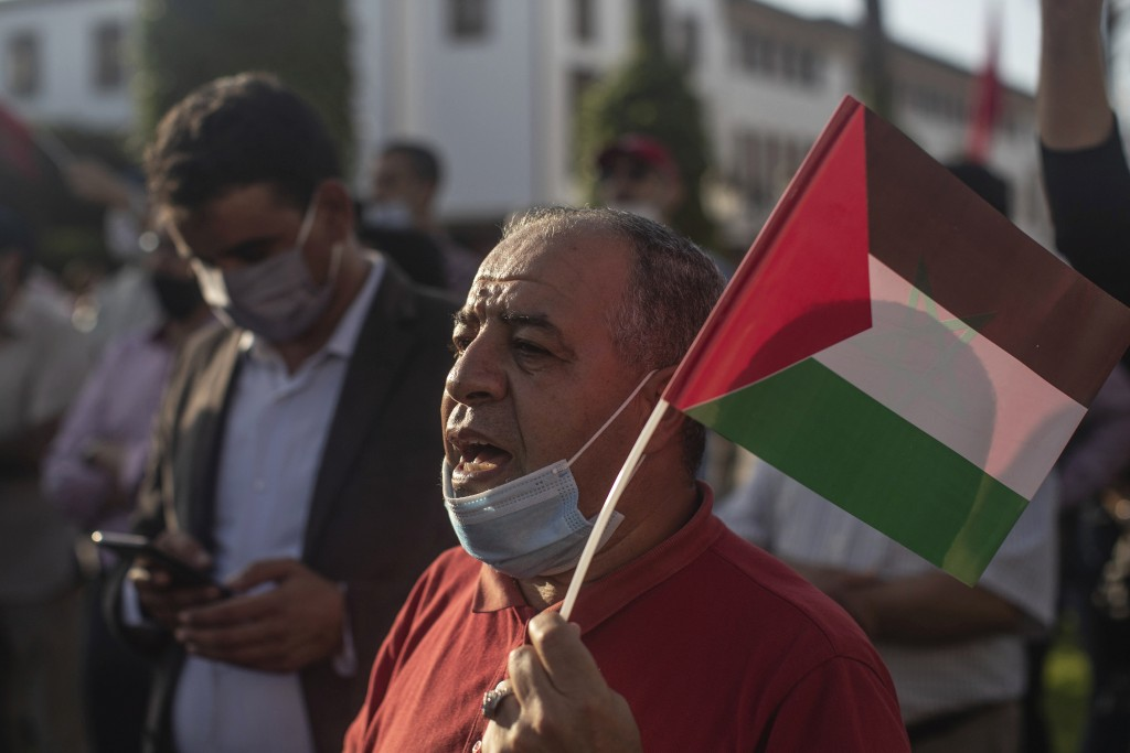 A man wearing a face mask chants slogans and holds a Palestinian flag during a protest against normalizing relations with Israel, in Rabat, Morocco, F...