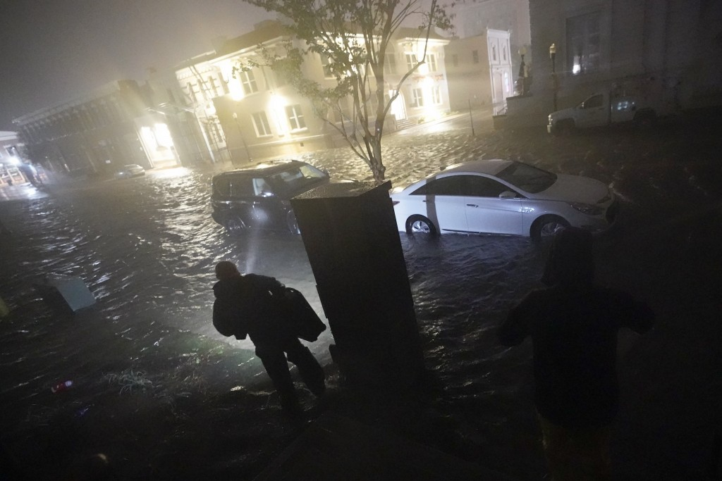 People use flashlights as they walk on flooded streets in search of their vehicle, Wednesday, Sept. 16, 2020, in Pensacola, Fla. Hurricane Sally made ...