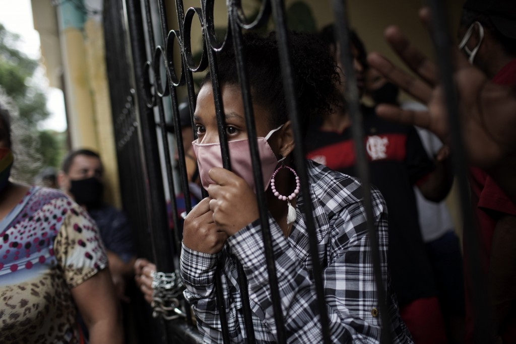 Squatters look from behind the iron gate of a house they occupy, before being evicted amid the new coronavirus pandemic in Rio de Janeiro, Brazil, Tue...