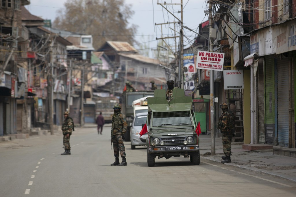 FILE - In this Tuesday, March 31, 2020, file photo, Indian army soldiers stand guard while they wait for a fellow soldier shopping during lockdown in ...