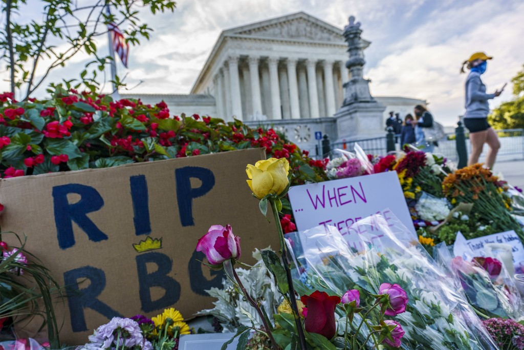People gather at the Supreme Court on the morning after the death of Justice Ruth Bader Ginsburg, 87, Saturday, Sept. 19, 2020 in Washington. (AP Phot...