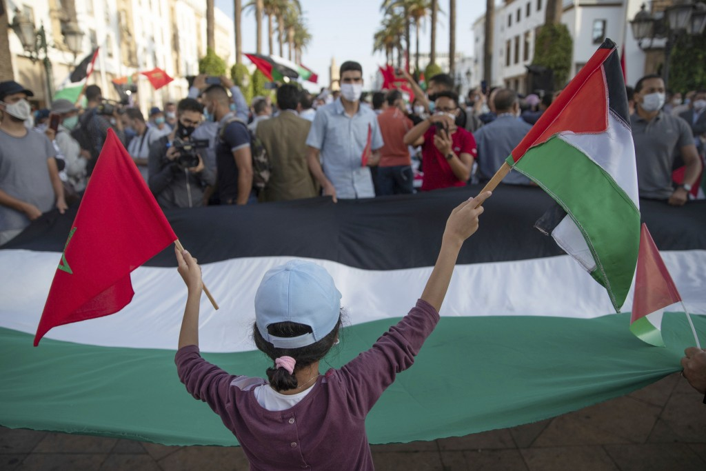 A young girl waves a Moroccan and a Palestinian flag during a protest against normalizing relations with Israel, in Rabat, Morocco, Friday, Sept. 18, ...