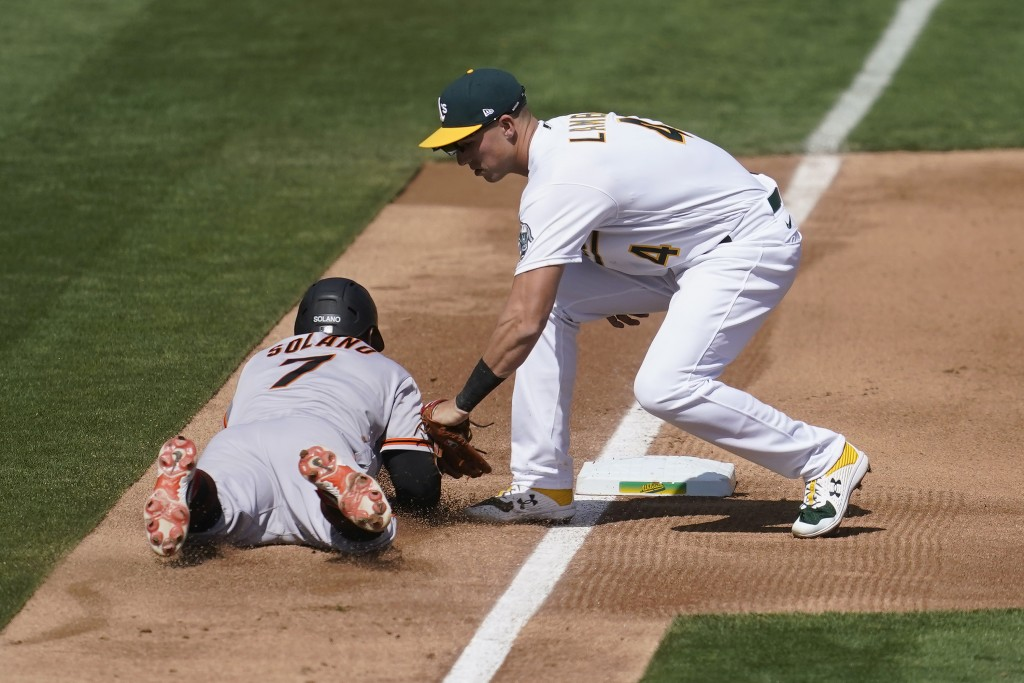 Oakland Athletics third baseman Jake Lamb, right, tags out San Francisco Giants' Donovan Solano during the fourth inning of a baseball game in Oakland...