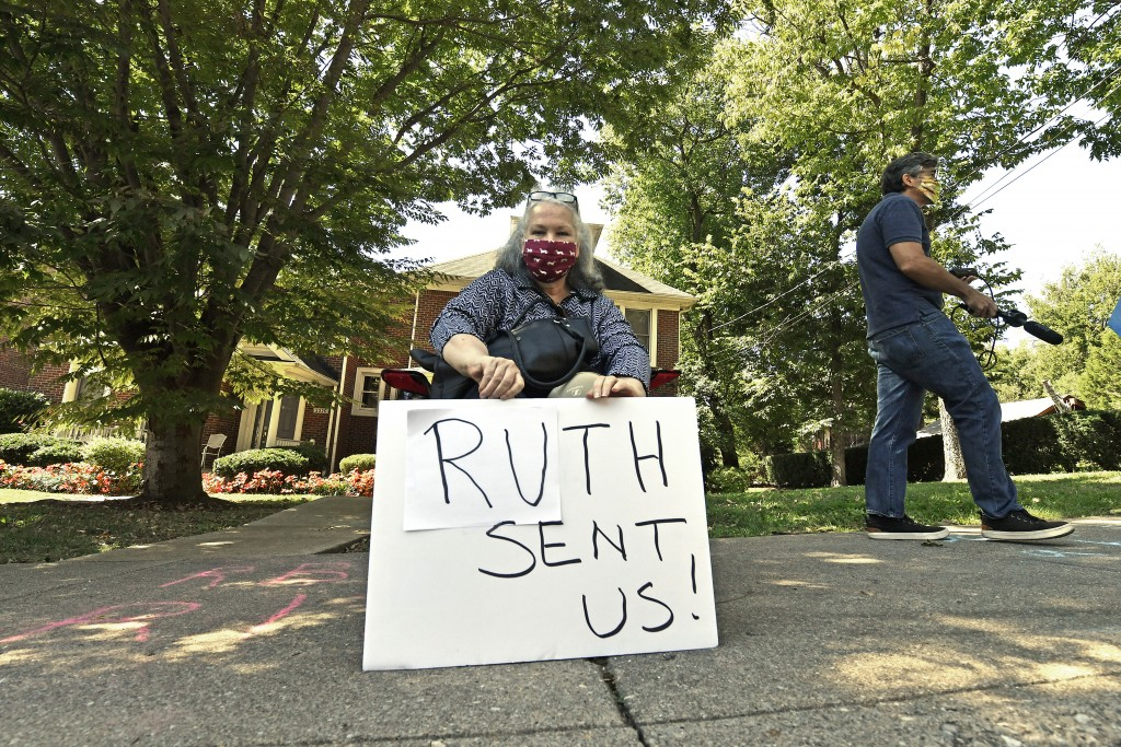 A protesters sits outside the house of Senate Majority Leader Mitch McConnell, R-Ky., in Louisville, Ky., Saturday, Sept. 19, 2020. McConnell vowed on...