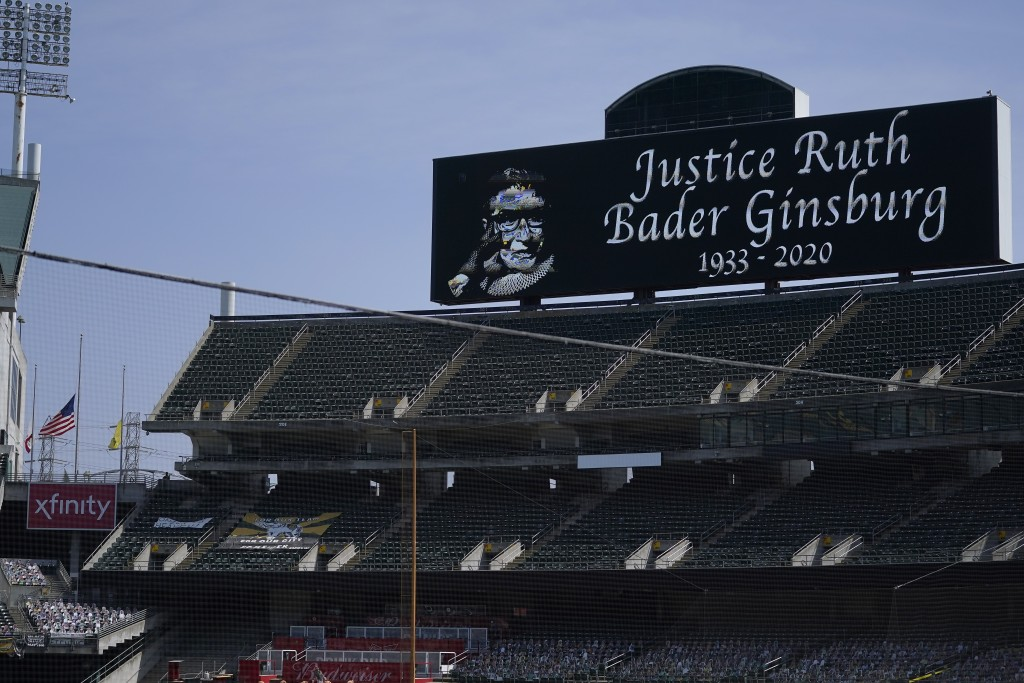 A flag flies at half-staff at Oakland Coliseum during a moment of silence for Supreme Court Justice Ruth Bader Ginsburg before a baseball game between...