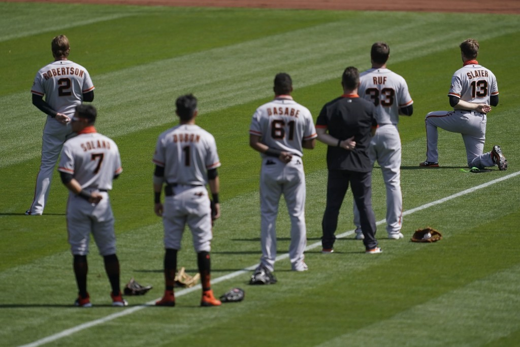San Francisco Giants' Austin Slater (13) kneels during the national anthem before a baseball game against the Oakland Athletics in Oakland, Calif., Sa...