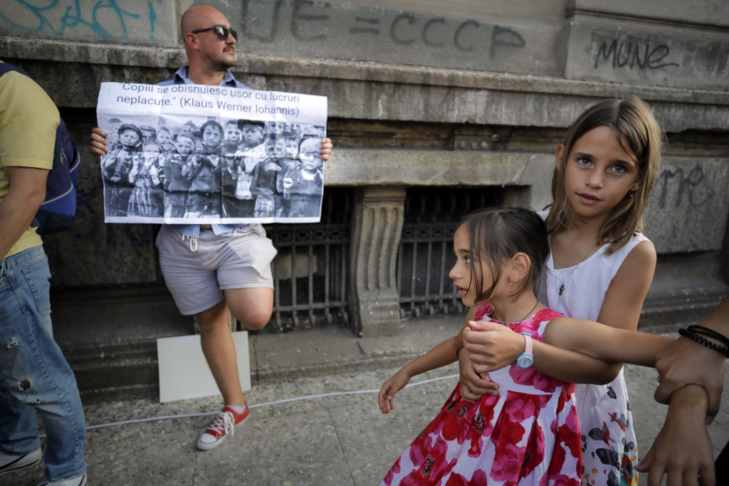 Children play next to a man holding a banner showing children in a concentration camp and a paraphrase from a statement by Romanian President Klaus Io...