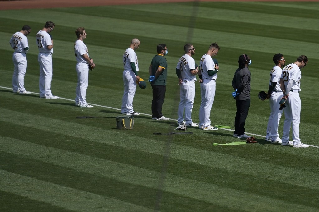 Oakland Athletics players and staff observe a moment of silence for Supreme Court Justice Ruth Bader Ginsburg before a baseball game against the San F...