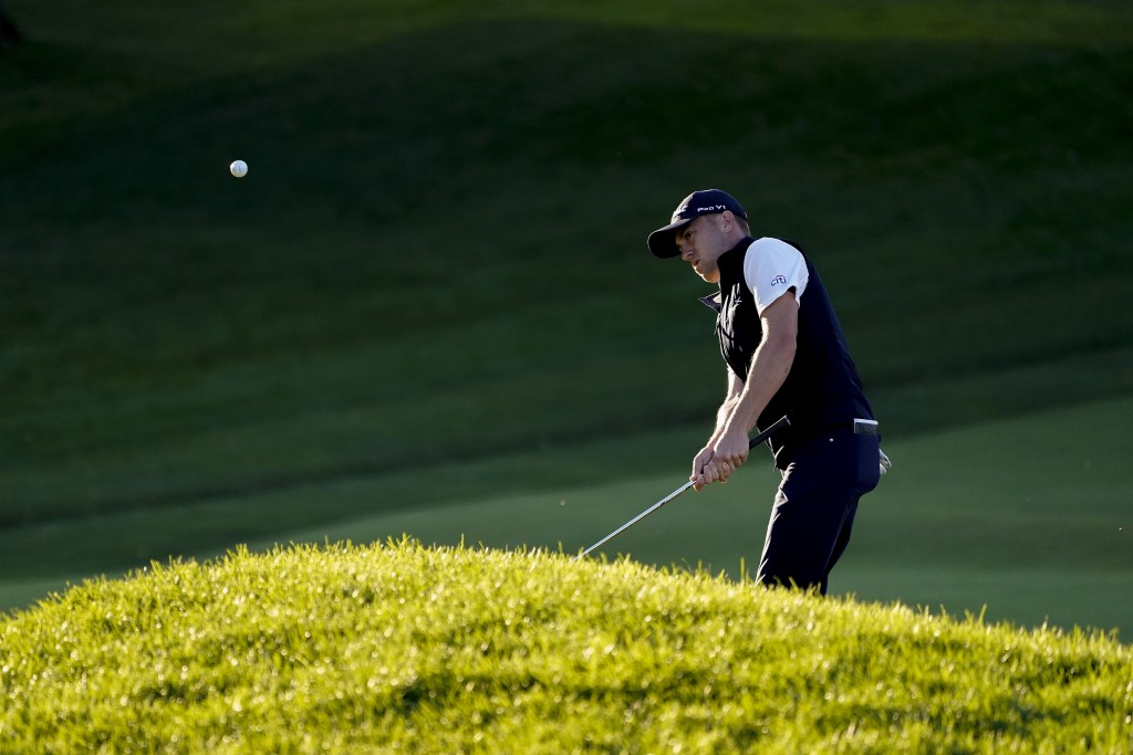 Justin Thomas, of the United States, chips onto the 18th green during the third round of the US Open Golf Championship, Saturday, Sept. 19, 2020, in M...