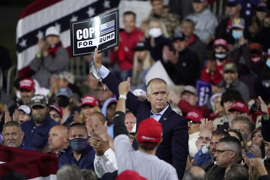 Sen. Tom Tillis, R-N.C. holds a sign as President Donald Trump speaks at a campaign rally, Saturday, Sept. 19, 2020 at the Fayetteville Regional Airpo...