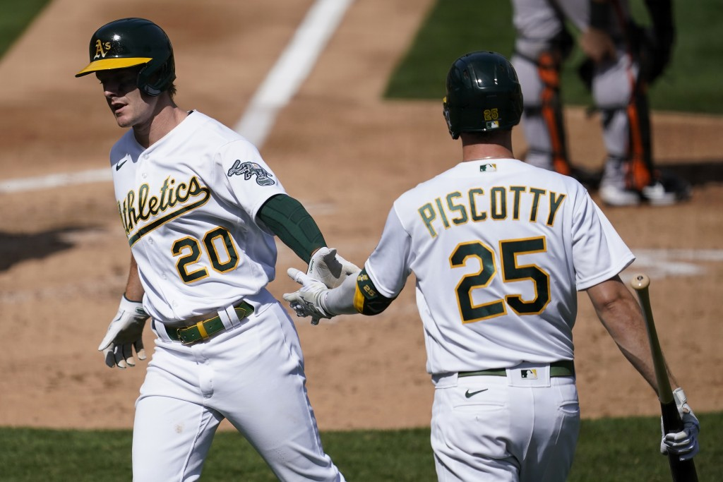 Oakland Athletics' Mark Canha (20) is congratulated by Stephen Piscotty after scoring against the San Francisco Giants in the fourth inning of a baseb...