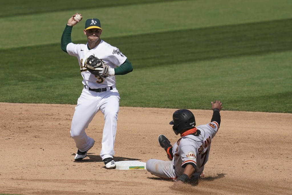 Oakland Athletics second baseman Tommy La Stella (3) throws to first base after forcing out San Francisco Giants' Donovan Solano at second base during...