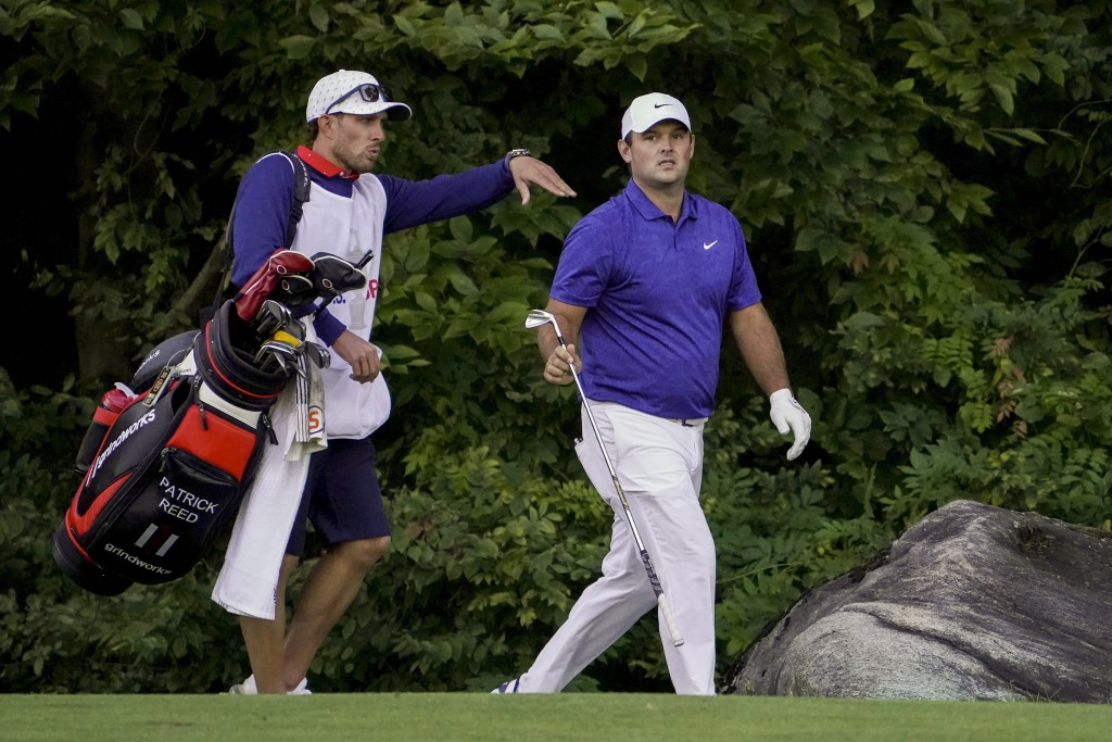 Patrick Reed, of the United States, hands a club to his caddie as they walk along the 15th fairway during the third round of the US Open Golf Champion...
