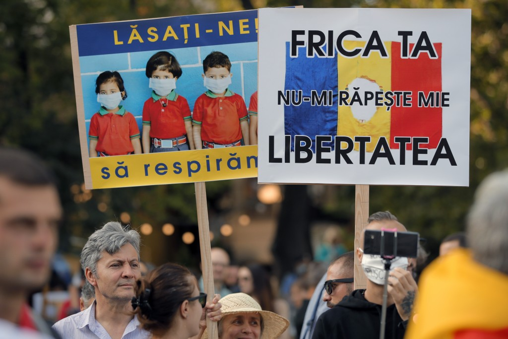 "People hold banners that read ""Let us breathe"" and ""Your fear won't take my freedom"" during a protest in Bucharest, Romania, Saturday, Sept. 19, 2020...."