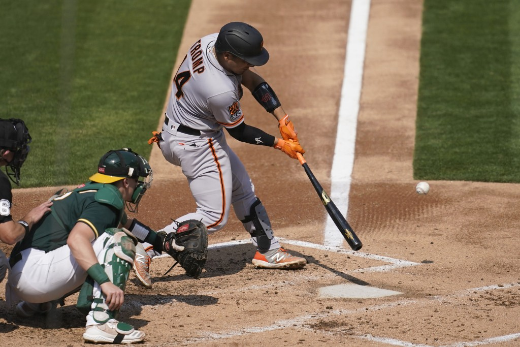 San Francisco Giants' Chadwick Tromp, right, hits a two-run home run in front of Oakland Athletics catcher Sean Murphy during the third inning of a ba...