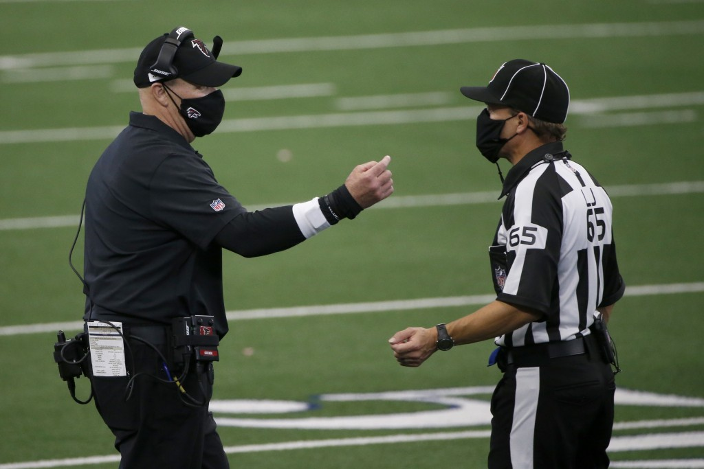 Atlanta Falcons head coach Dan Quinn talks with referee Walt Coleman (65) in the second half of an NFL football game against the Dallas Cowboys in Arl...