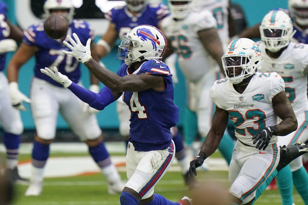 Buffalo Bills wide receiver Stefon Diggs (14) catches a pass ahead of Miami Dolphins cornerback Noah Igbinoghene (23), during the first half of an NFL...