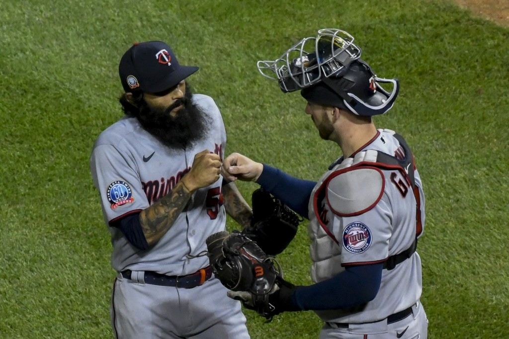 Minnesota Twins relief pitcher Sergio Romo, left, and catcher Mitch Garver, right, celebrate at end of a baseball game against the Chicago Cubs Sunday...