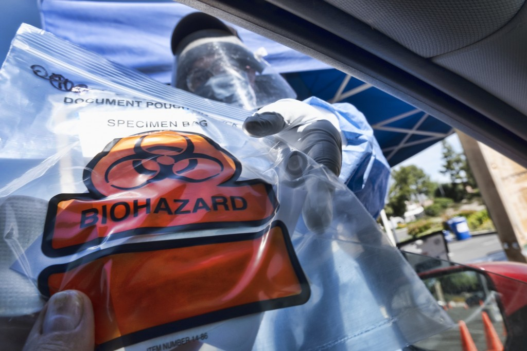 FILE -In this May 6, 2020 photo a medical worker hands a self administered coronavirus test to a patient at a drive through testing site in a parking ...
