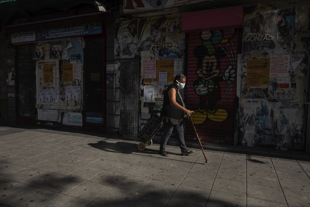 A woman wearing a face mask to prevent the spread of the coronavirus walks in the southern neighbourhood of Vallecas in Madrid, Spain, Monday, Sept. 2...