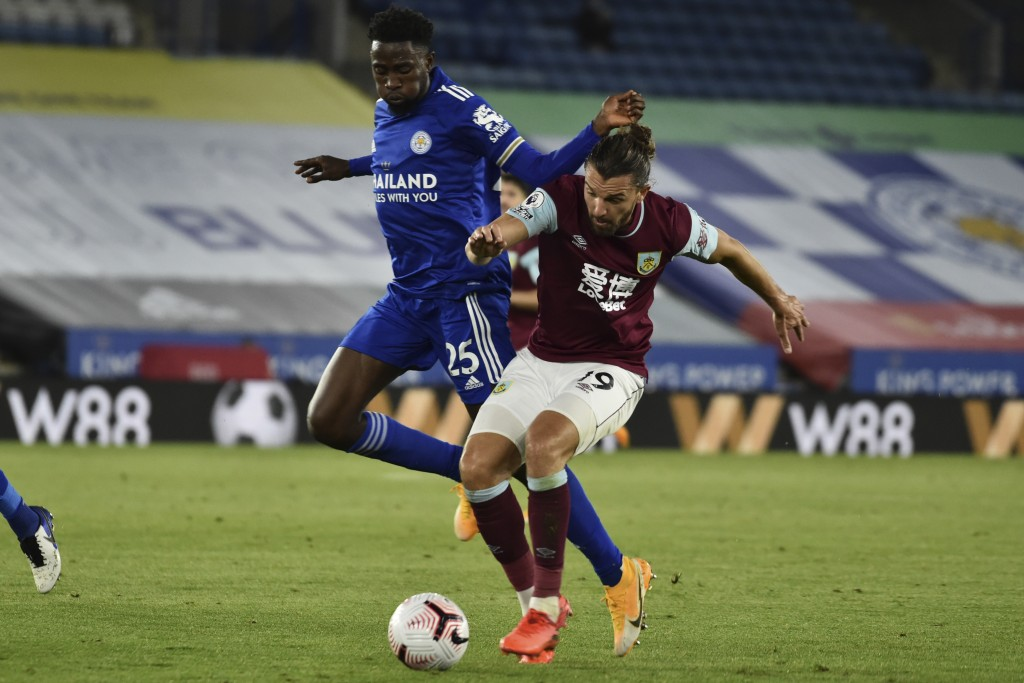 Leicester's Wilfred Ndidi, left, vie for the ball with Burnley's Jay Rodriguez during the English Premier League soccer match between Leicester City a...