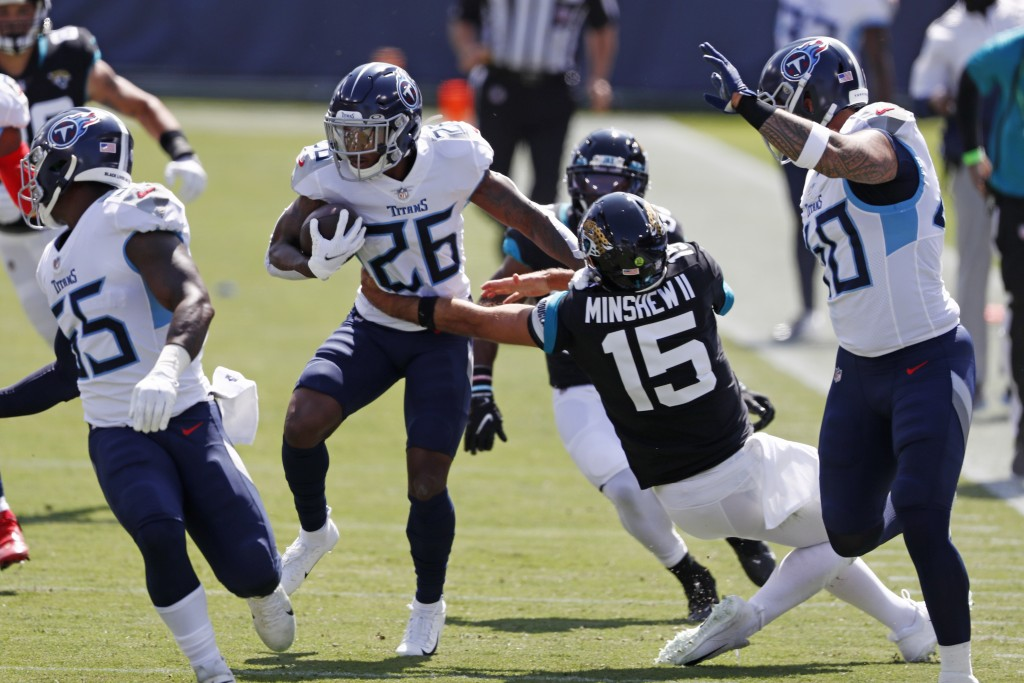 Tennessee Titans cornerback Kristian Fulton (26) runs back an interception as Jacksonville Jaguars quarterback Gardner Minshew (15) tries to tackle hi...