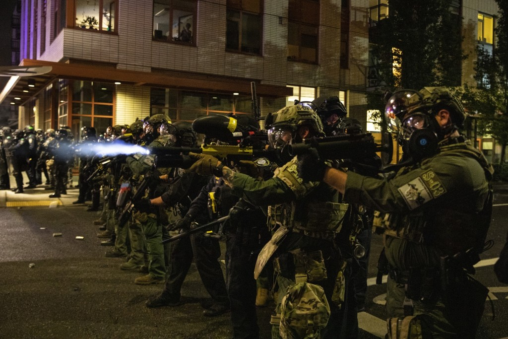 FILE - In this Friday, Sept. 18, 2020, file photo, Federal police try to take control of the streets during protests in Portland, Ore. The protests, w...